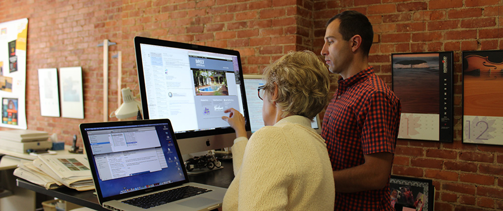 Teresa Angelo and Greg Montano work on a website.